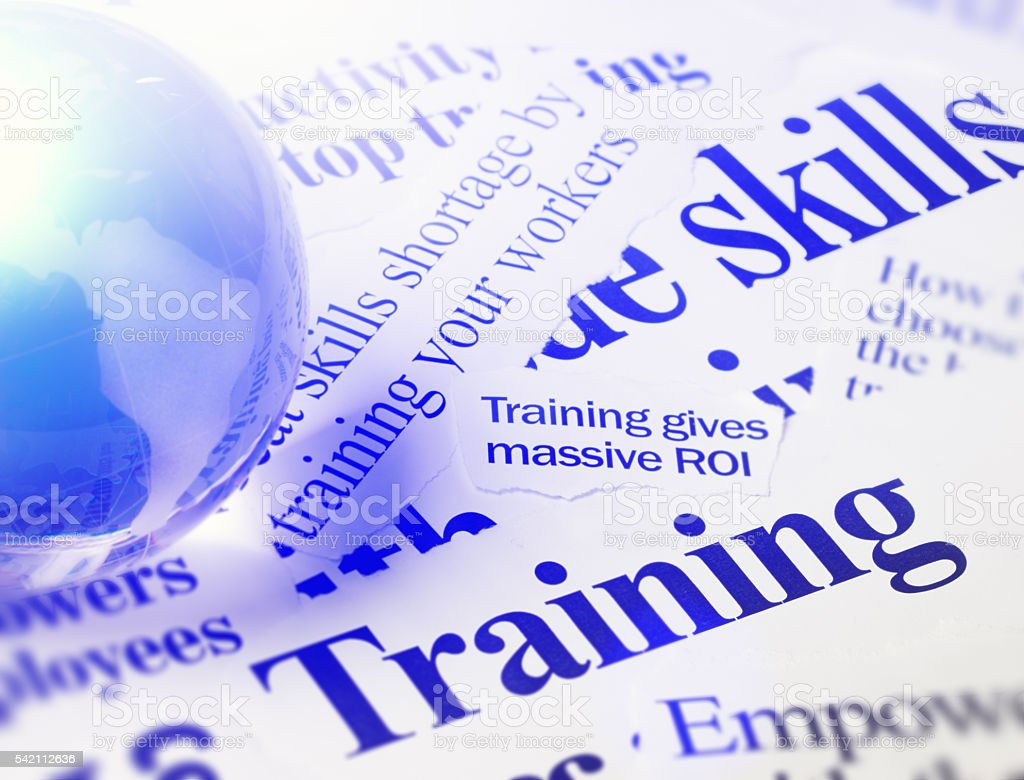 Newspaper headlines on skills and training with glass globe stock photo
