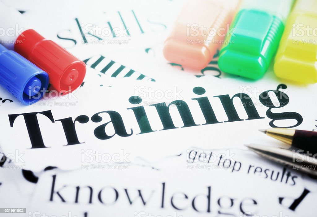 Newspaper headlines on training, skills, knowledge, and results, plus pens stock photo