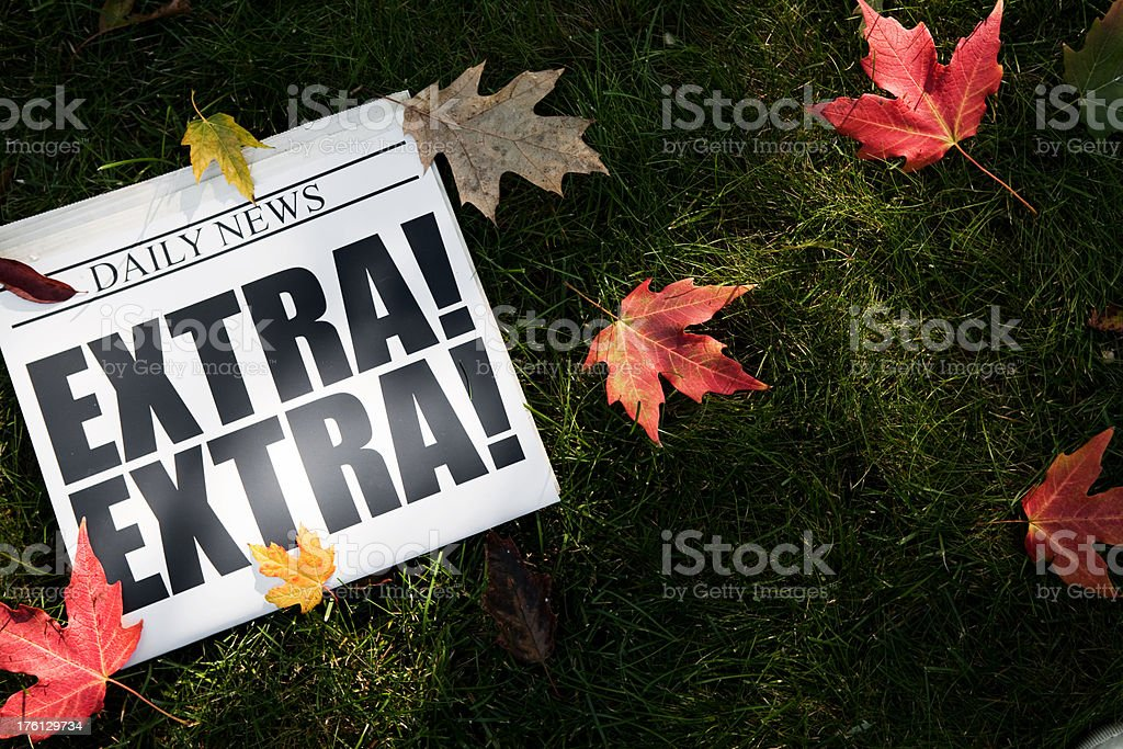 EXTRA! Newspaper on Grass with Autumn Leaves royalty-free stock photo