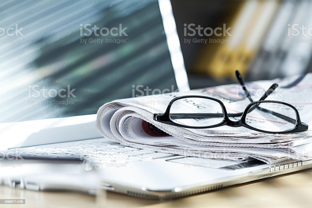 Newspaper on laptop stock photo