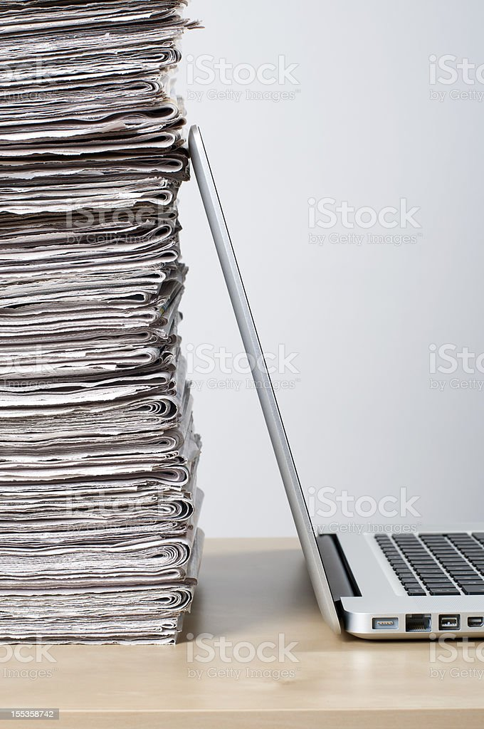 Newspaper pile and laptop depicting online news concept stock photo