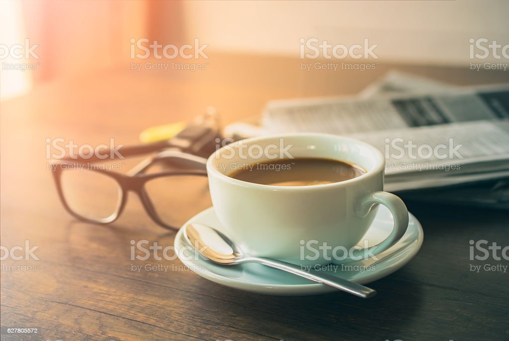 Newspaper reading glasses coffee cup and mobile phone on busines stock photo