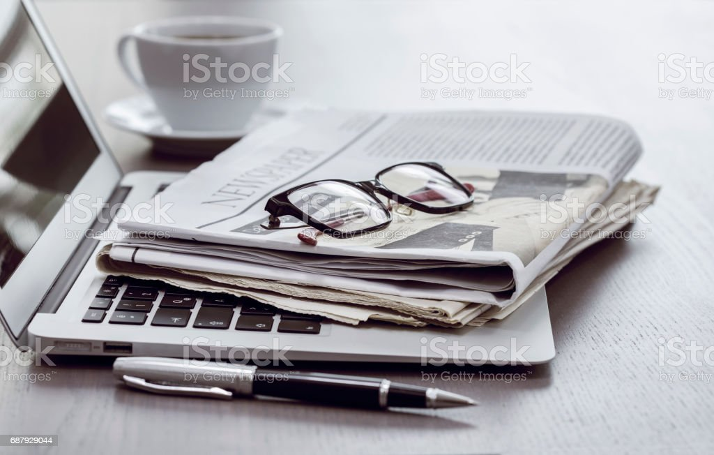 Newspaper with computer on table stock photo