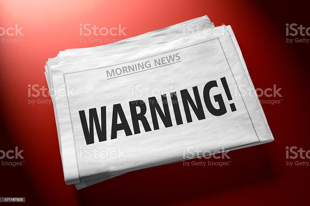 Newspaper with Warning! word on first page stock photo