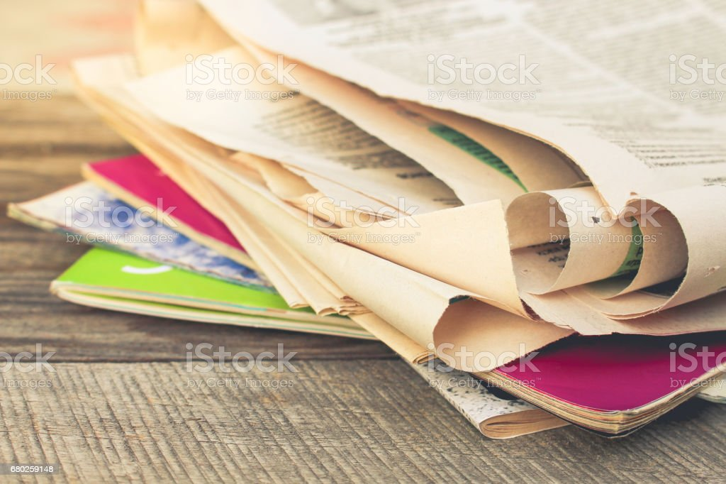 Newspapers and magazines on old wood background. Toned image. stock photo