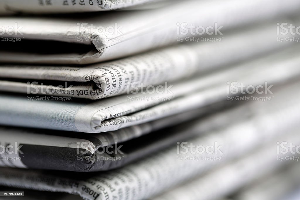Newspapers folded and stacked concept stock photo