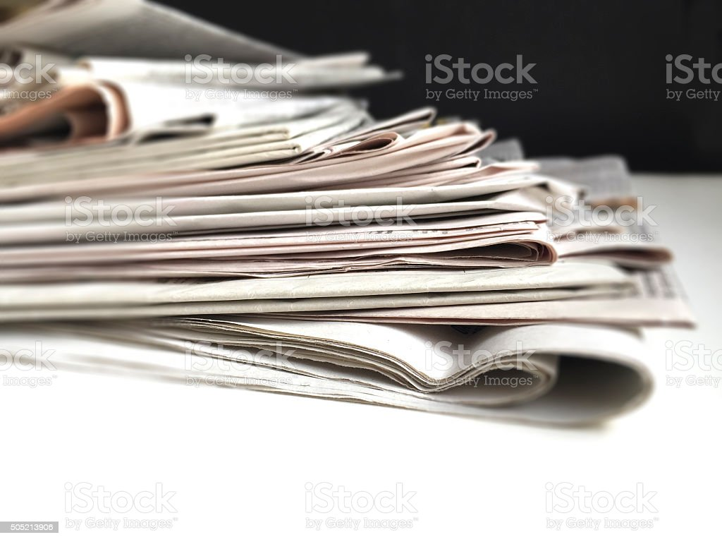 Newspapers in Messy Stack stock photo