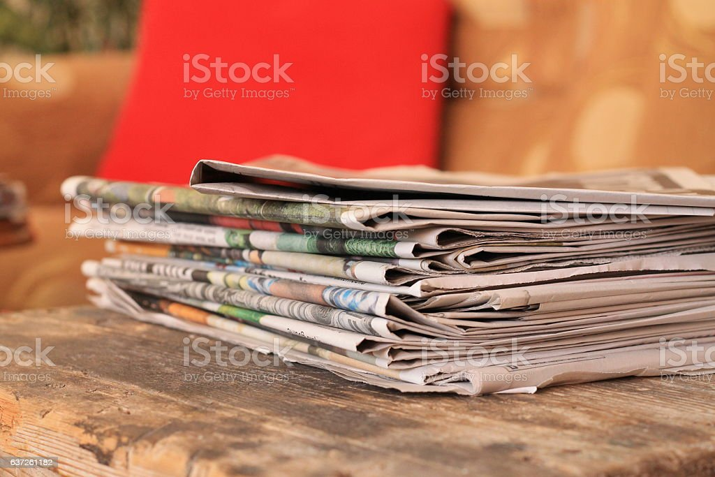 Newspapers on wooden table stock photo