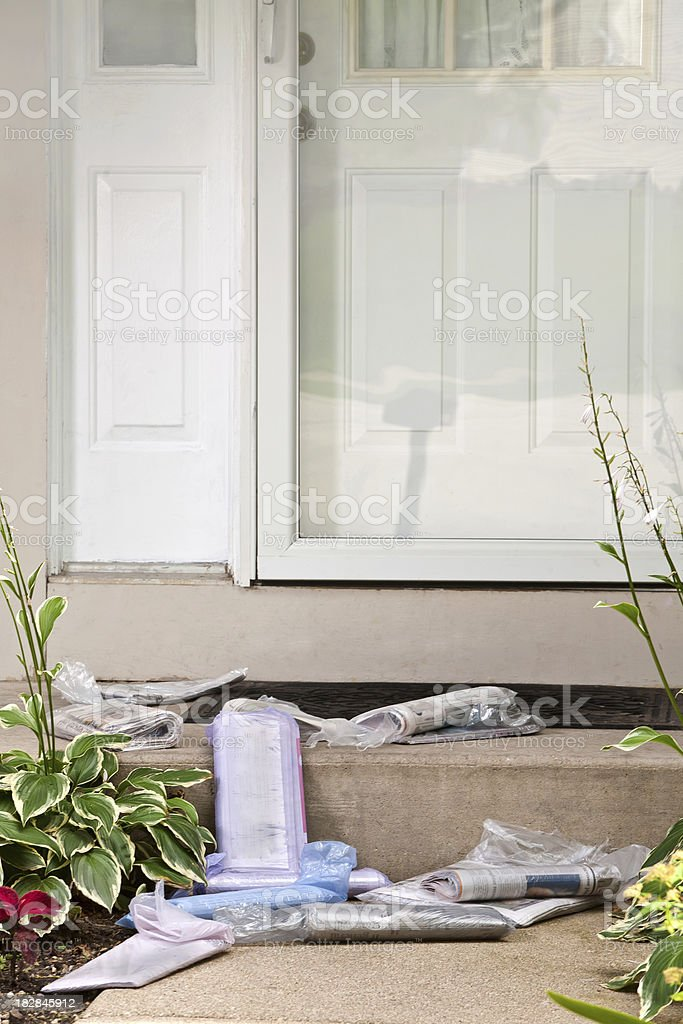 newspapers piled on stoop stock photo