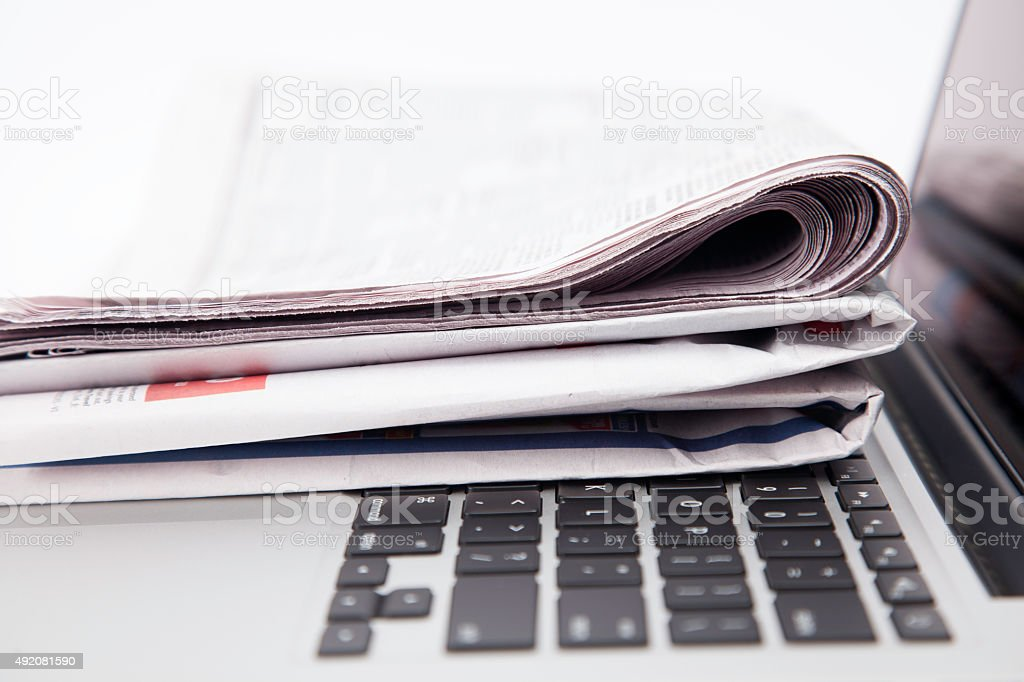 Newspapers resting on laptop keyboard stock photo