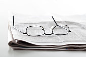 Newspapers with eyeglasses on table