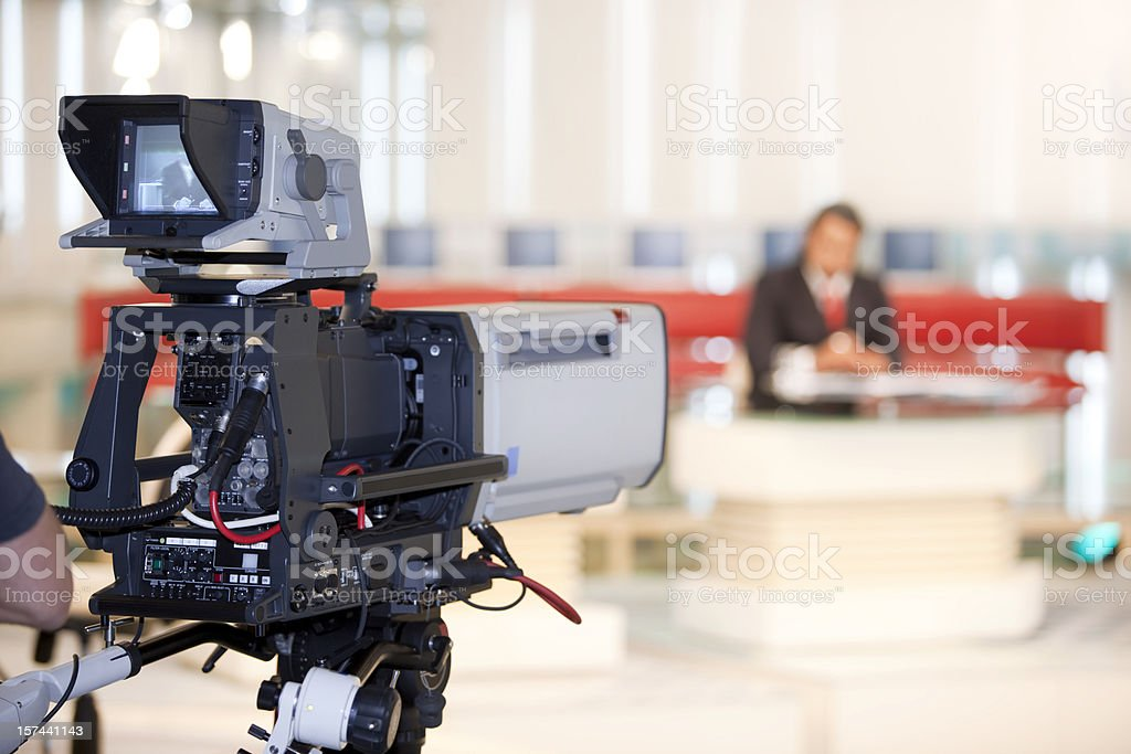 Newsreader in front of television camera stock photo