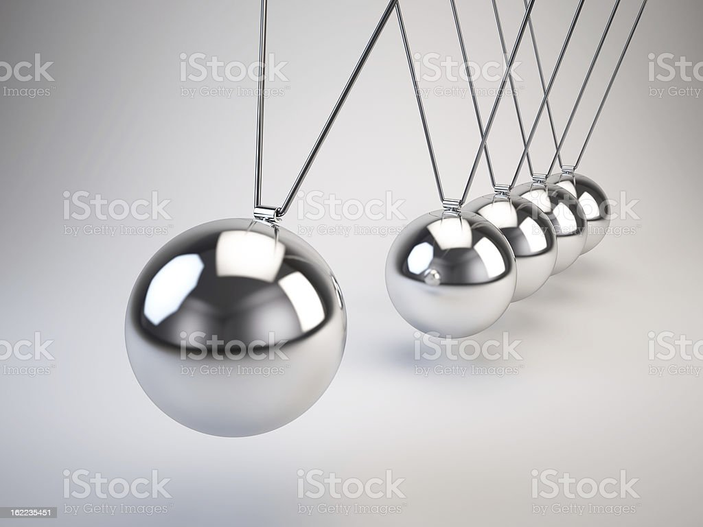 Newton's cradle of balancing balls swinging side to side stock photo
