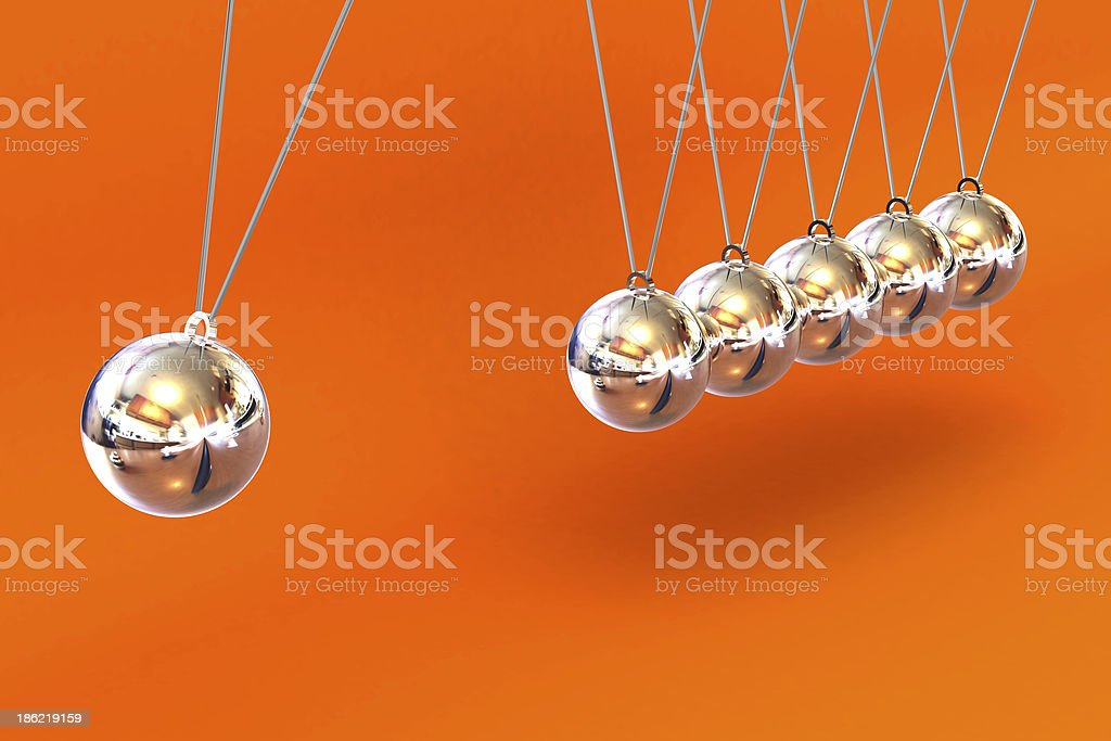 Newtons Cradle on a Orange Background royalty-free stock photo
