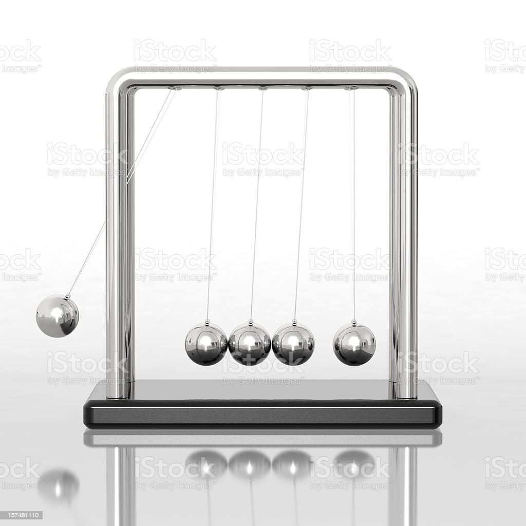 Newton's cradle sitting on a reflective desk stock photo