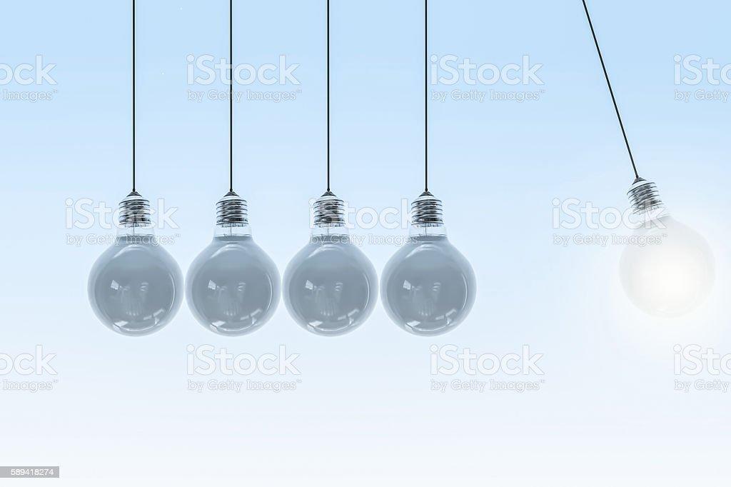 Newtons cradle - swinging light bulb stock photo