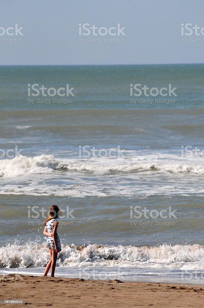 Ni?a adolescente mirando en el horizonte en una playa stock photo