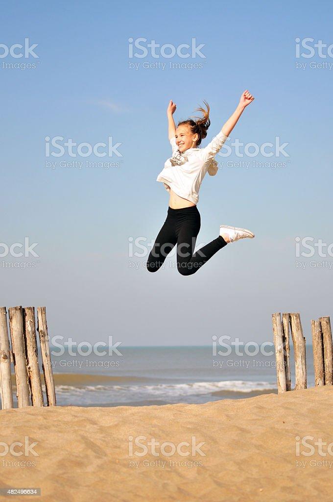 Ni?a feliz saltando en la playa stock photo