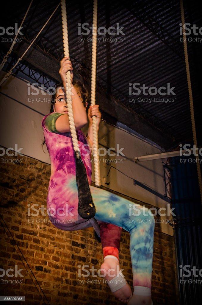 Niña gimnasta sentada trapecio stock photo