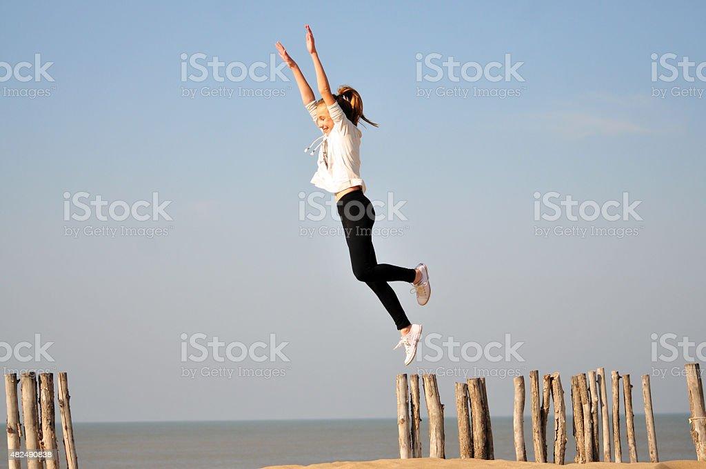Ni?a haciendo equilibrio sobre troncos en la playa stock photo