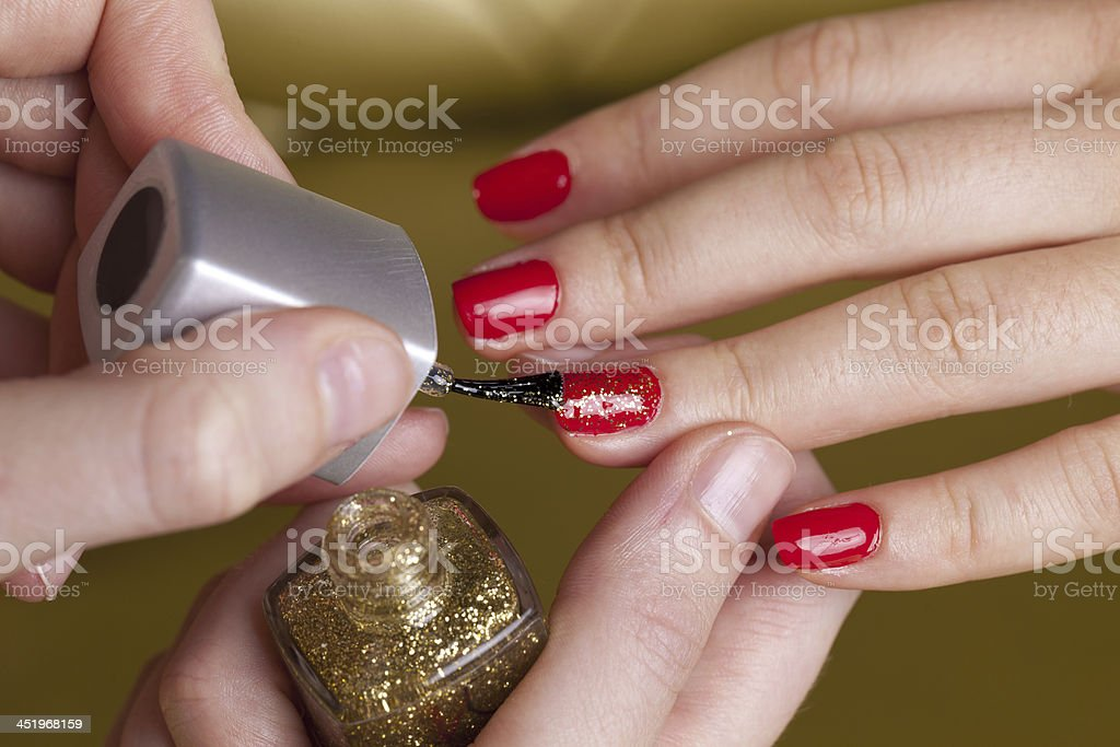 Nial red polish and golden sparks on female