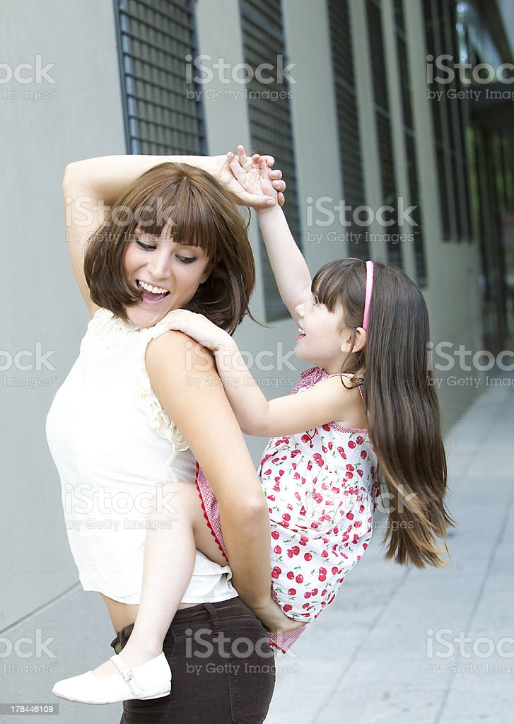 Nice girl climb to the back of her mother stock photo