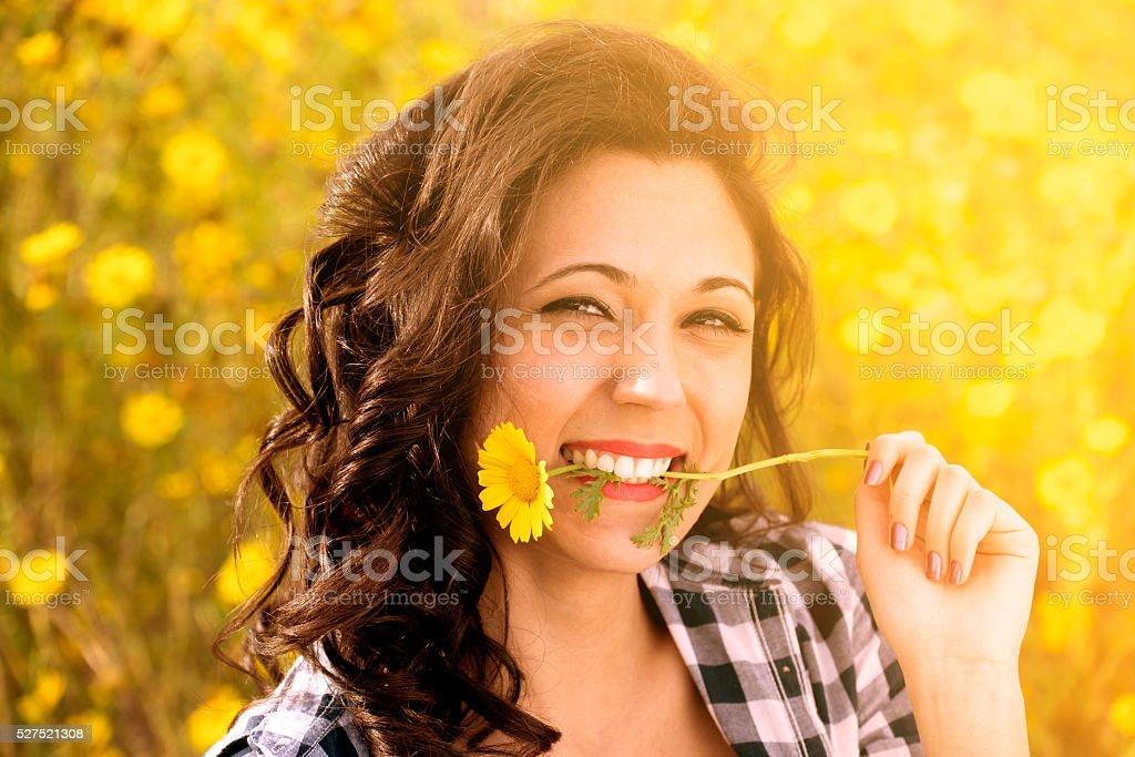 nice girl plays biting a daisy as a joke stock photo