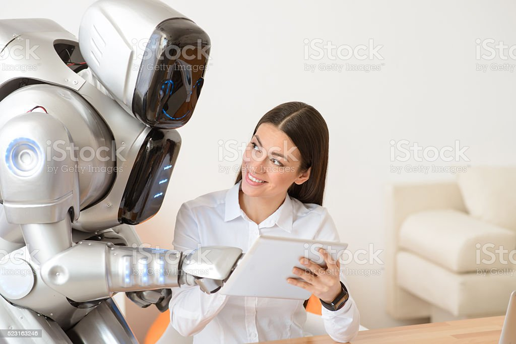 Nice girl using tablet with robot stock photo