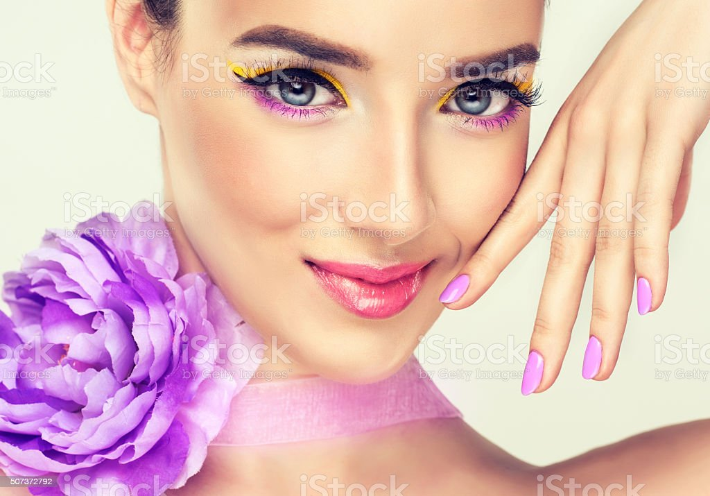 Nice girl with bright make up and violet flower. stock photo