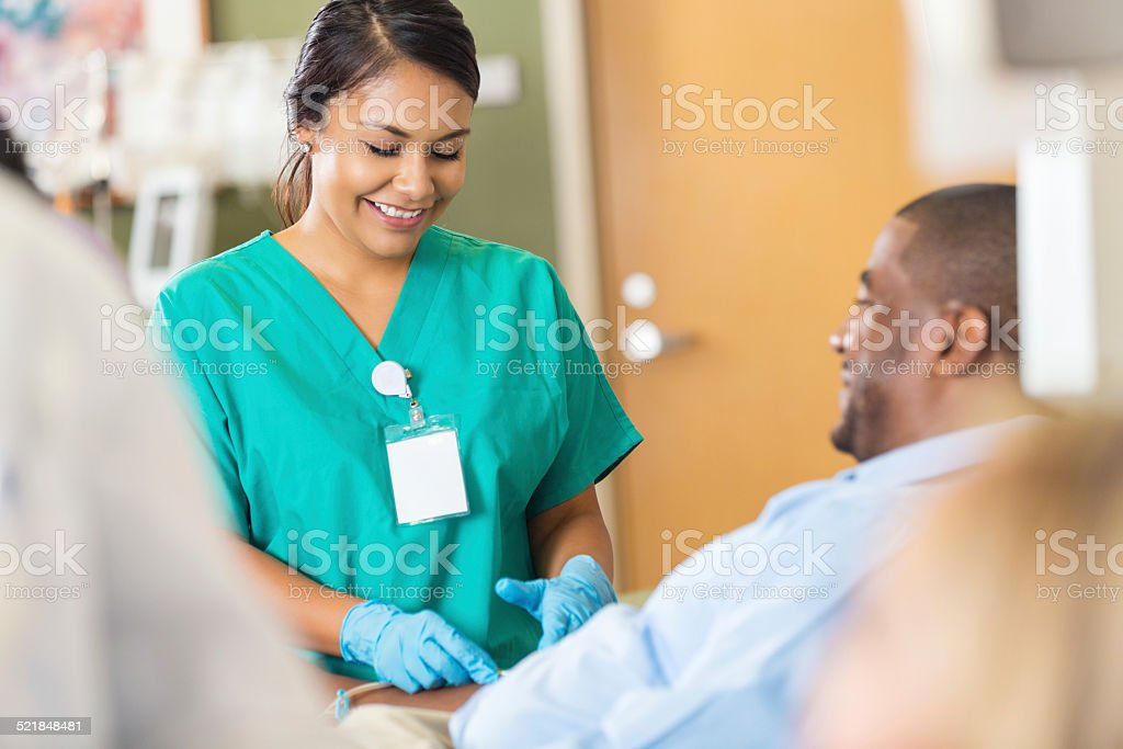 Nice hospital phlebotomist taking a sample from a patient stock photo