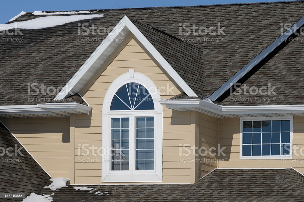 Nice House with Gabled Asphalt Shingle Roof and Snow stock photo