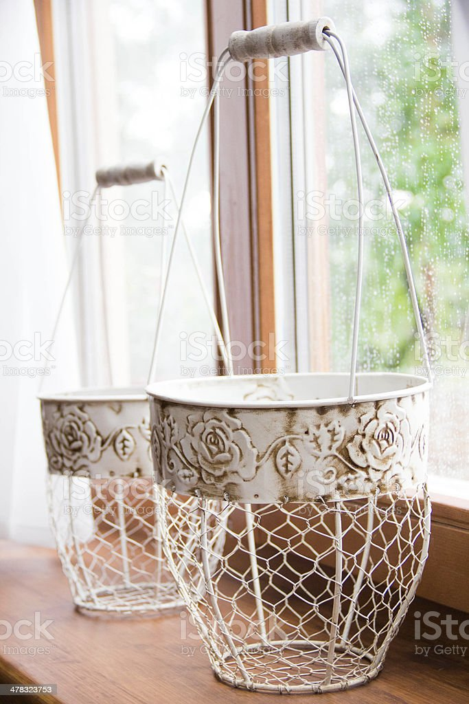 Nice iron baskets for flowers on the windowsill at home royalty-free stock photo