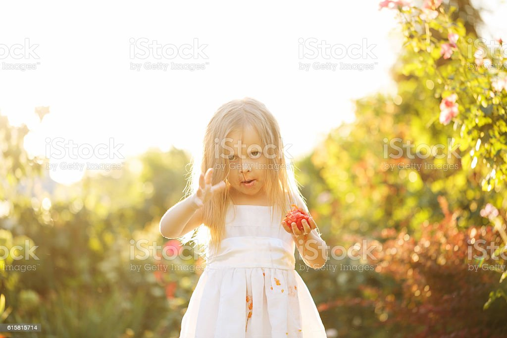 Nice little girl eating a tomato. stock photo