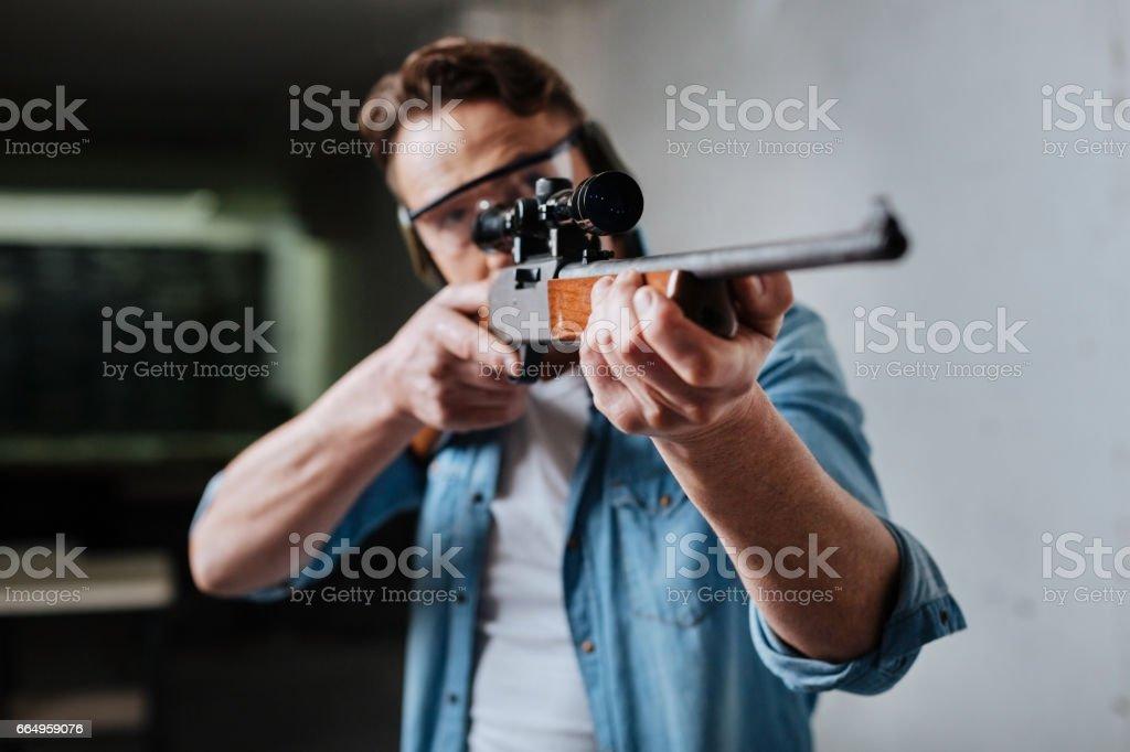 Nice pleasant man developing his shooting skills stock photo