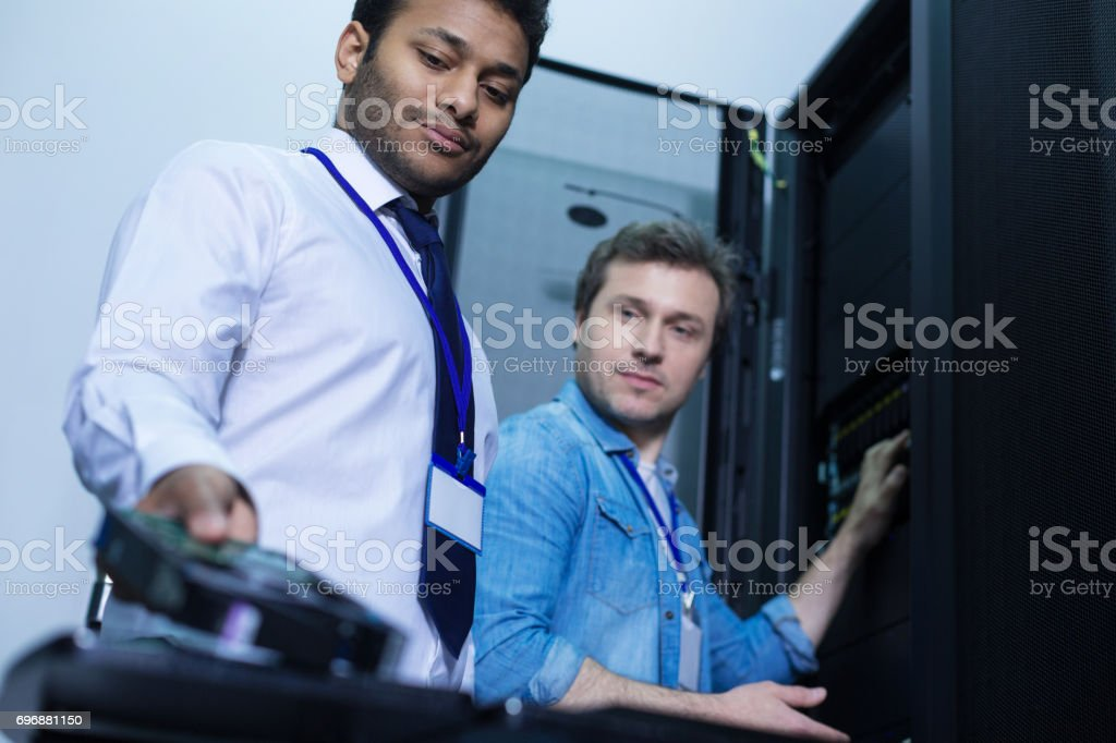 Nice positive engineers looking at the rack server stock photo