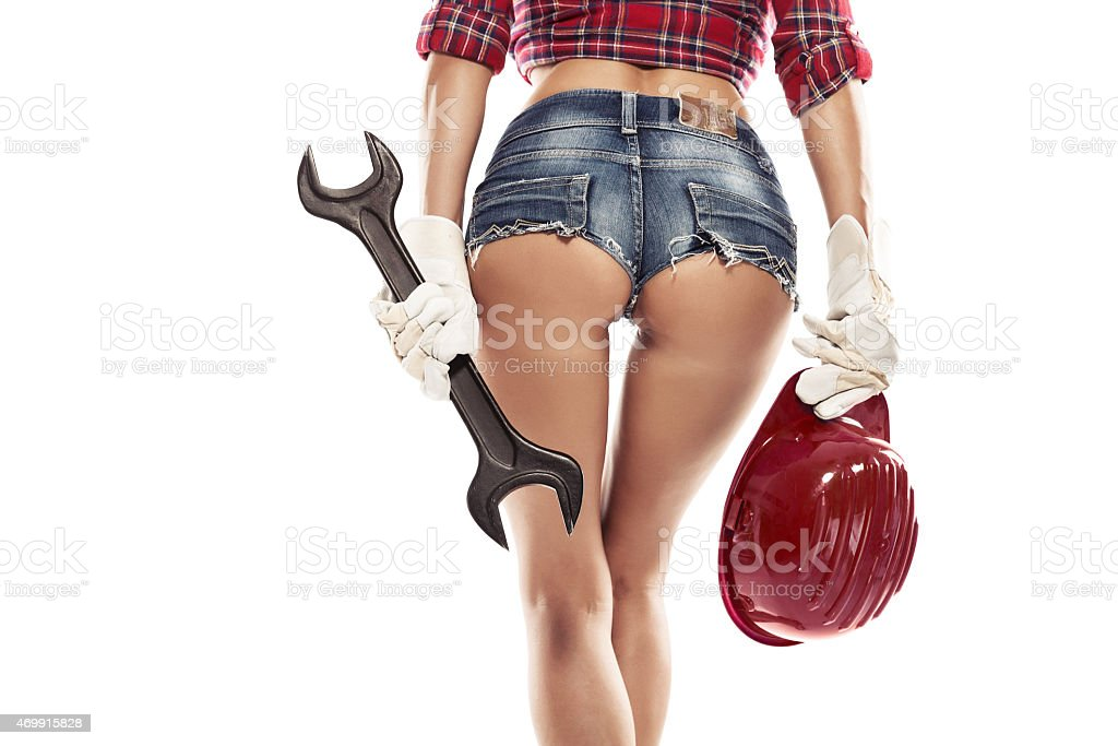 Nice sexy woman mechanic showing  bum buttock and holding wrench stock photo