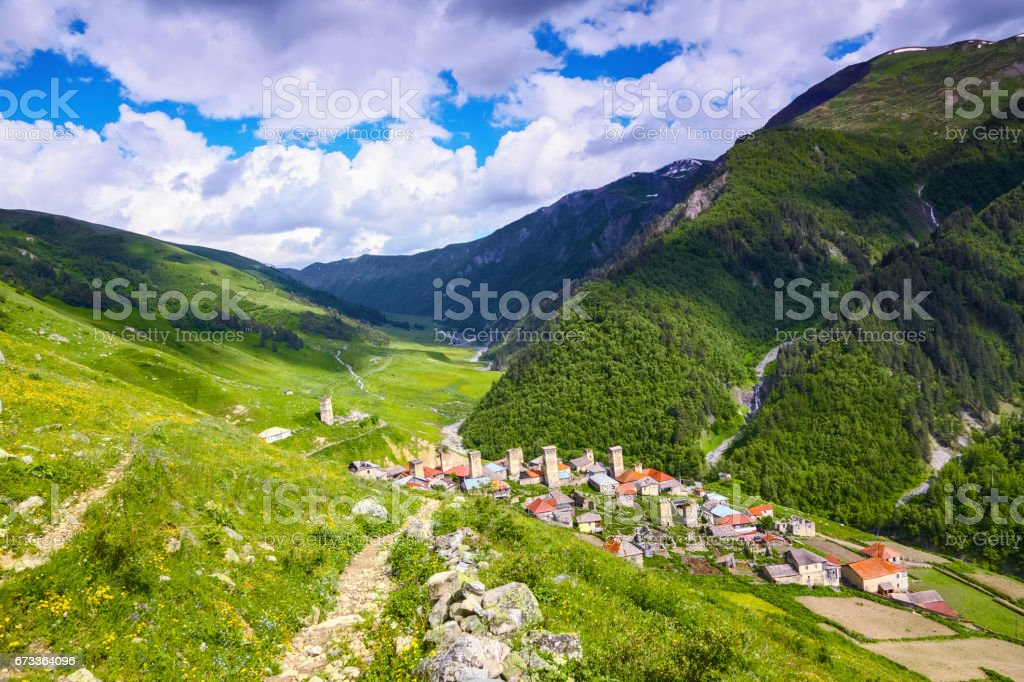 A nice small Georgian village with towers situated among high mountains covered with forests, meadows with flowers and river. Upper Svaneti, Europe. stock photo