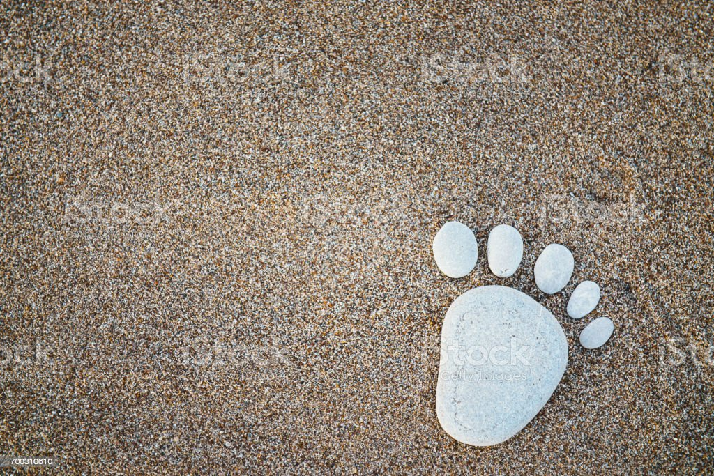 Nice stone made footprint on the sand shore, background. stock photo