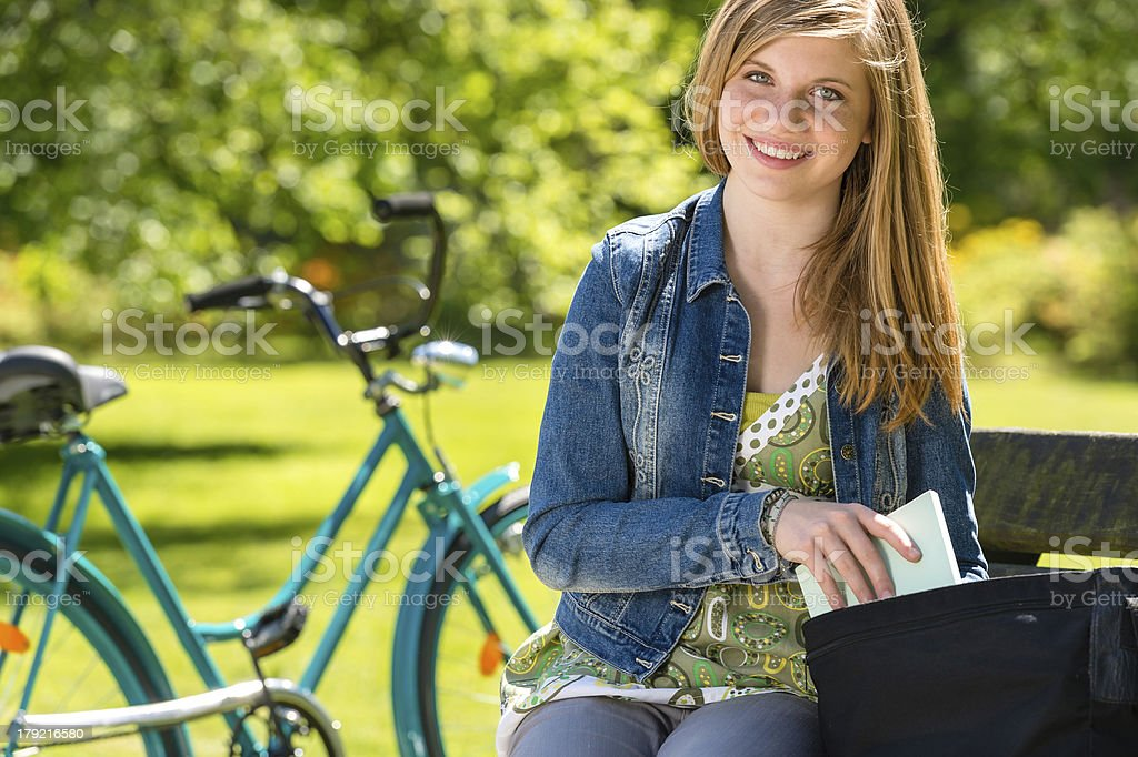 Nice student girl sitting in the park royalty-free stock photo