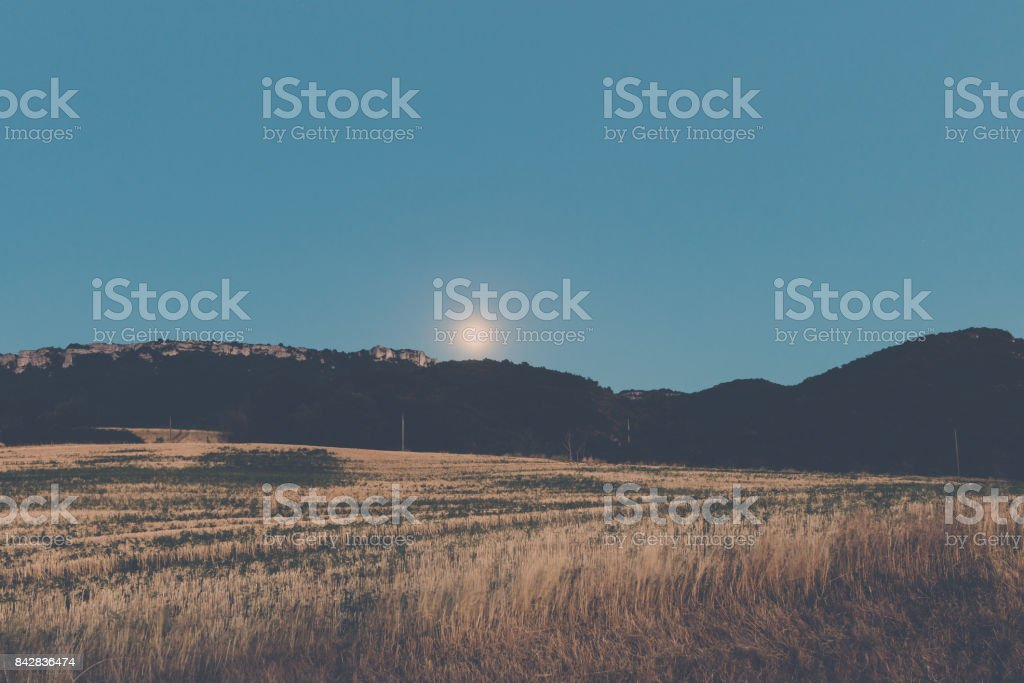 Nice view over the mountains and fields in the hills underneath an emerging moon stock photo