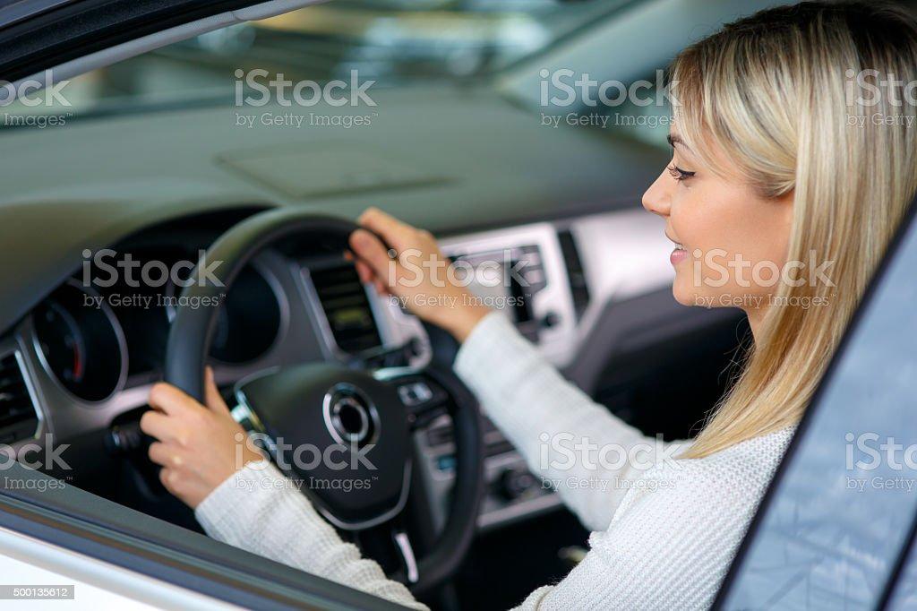Nice woman choosing a car in auto show stock photo