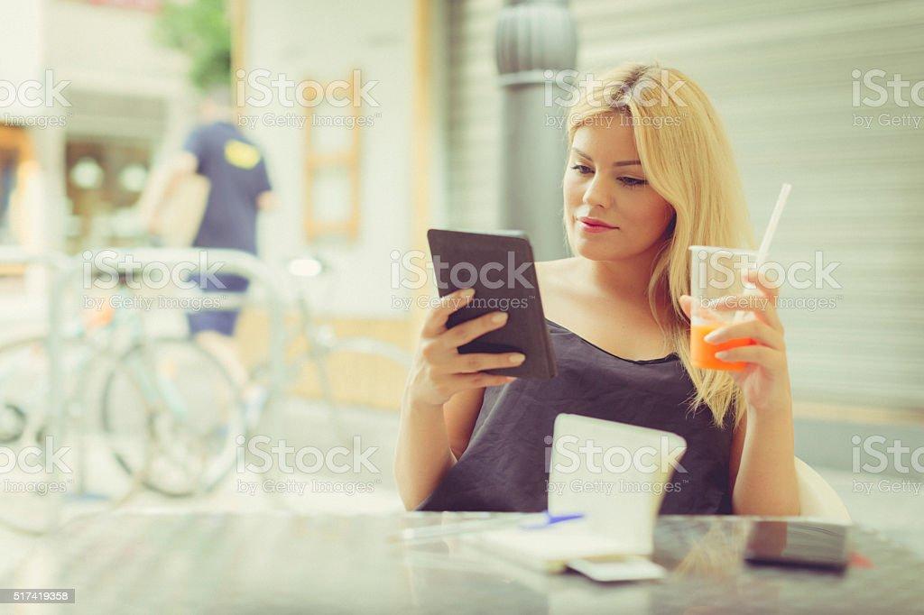 Nice woman reading an ebook outdoor at bar stock photo