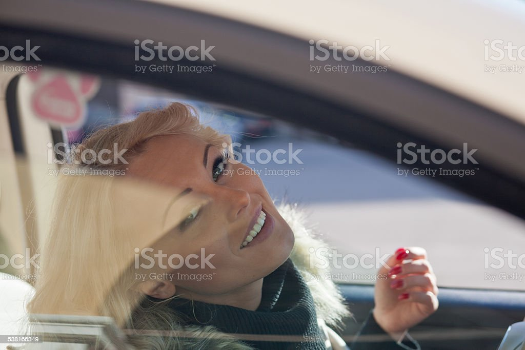 nice woman smiling you from her car stock photo