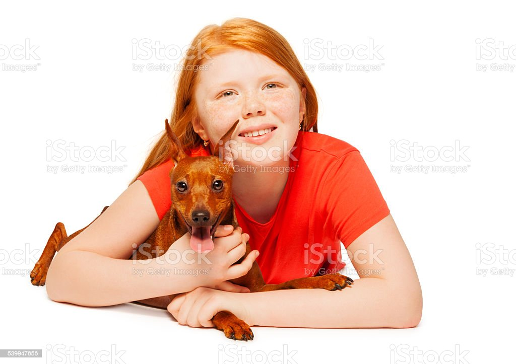 Nice young girl with her dog lay down portrait stock photo