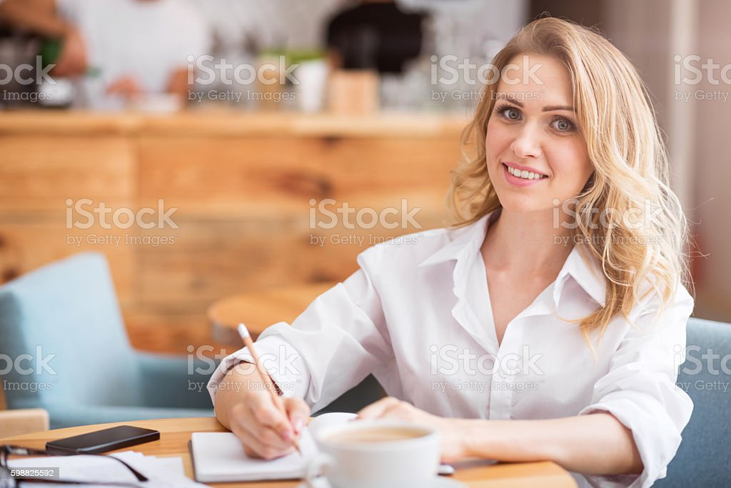 Nice young woman writing something down stock photo