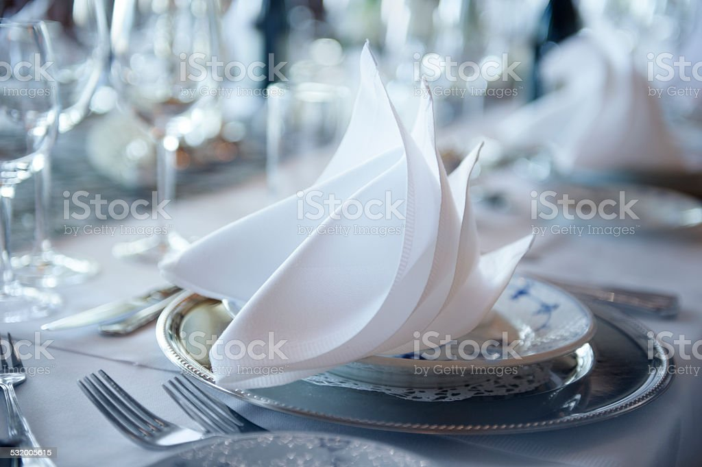 Nicely covered up for dinner with plates glass and napkin stock photo
