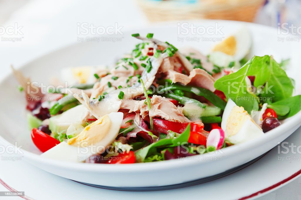 Nicoise salad in a white bowl on a white plate stock photo