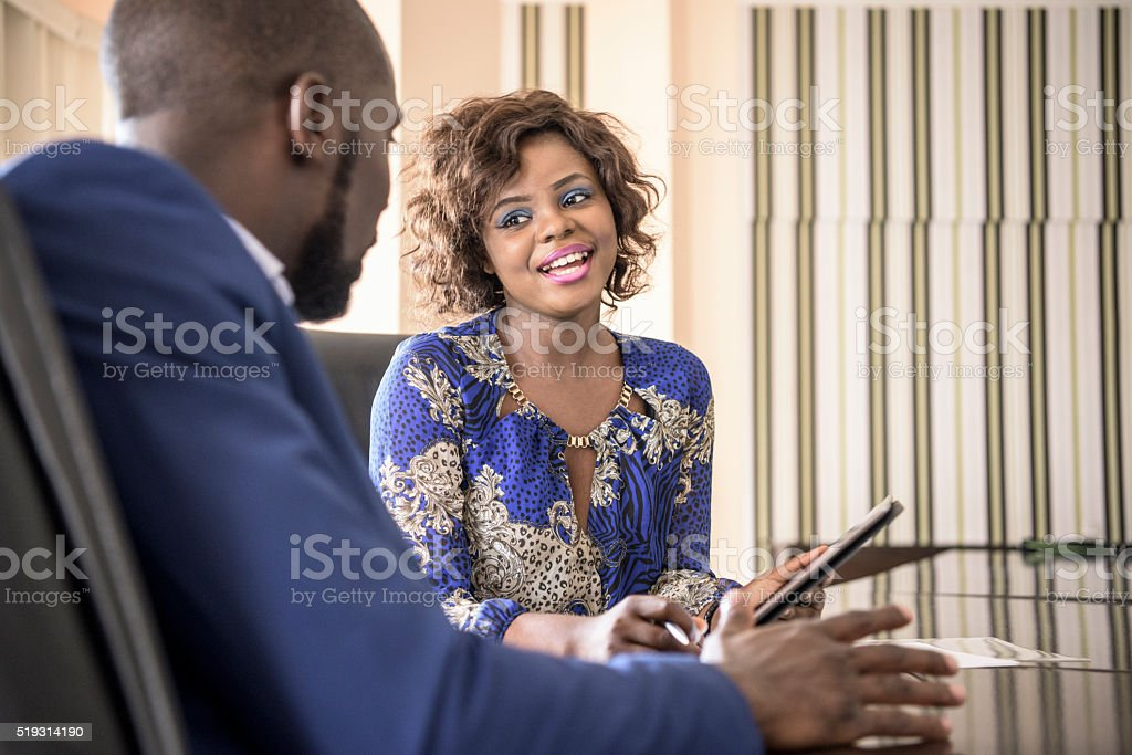 Nigerian businesswoman smiling at male colleague in meeting stock photo