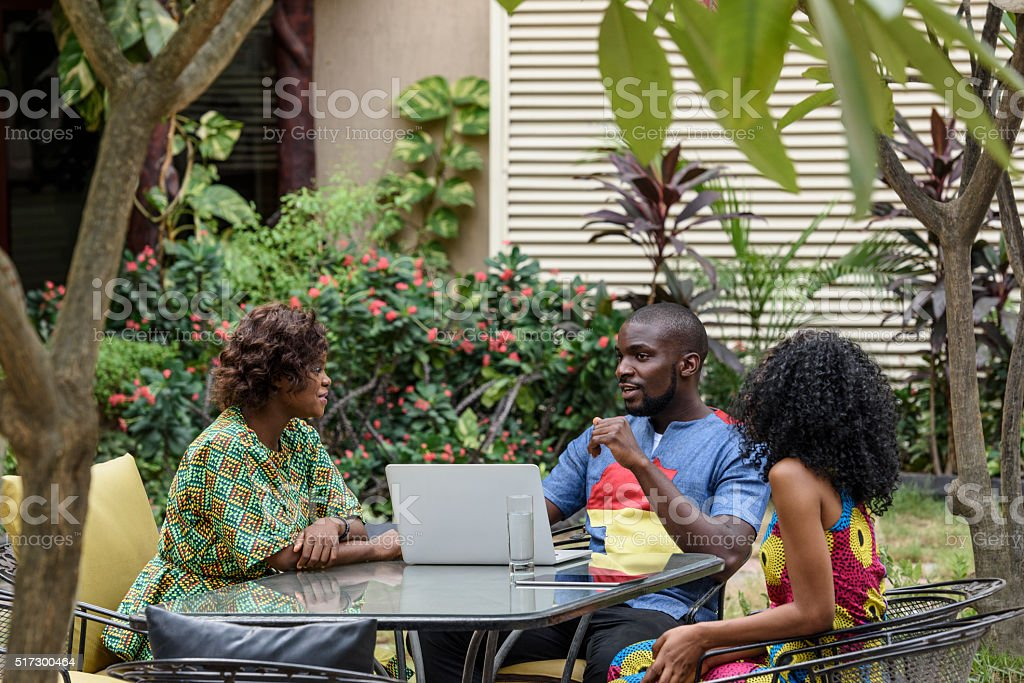 Nigerian colleagues with laptop talking in garden stock photo