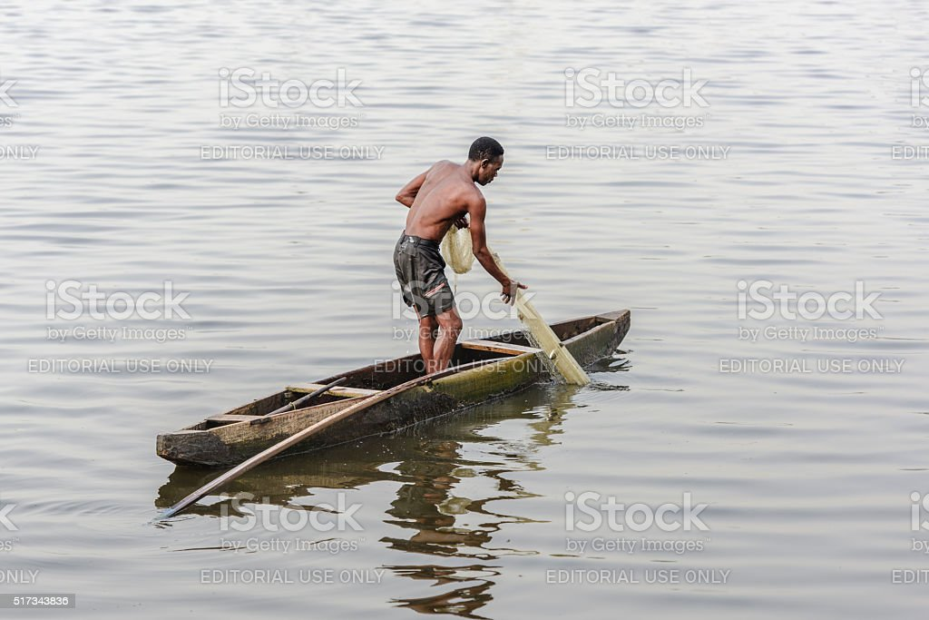 Nigerian fisherman pulling his fishing net from the water, Lagos stock photo